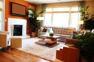 Warm, sunny living room with fireplace, TV and large window